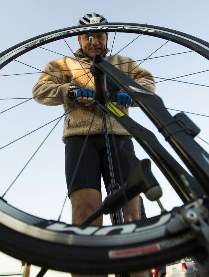 Detlef Ross with Team Ion airs up his tires as he prepares to begin his journey from Tully stadium, one of three starting points, to Austin during the BP MS 150 on Saturday, April 20, 2013, in Houston.