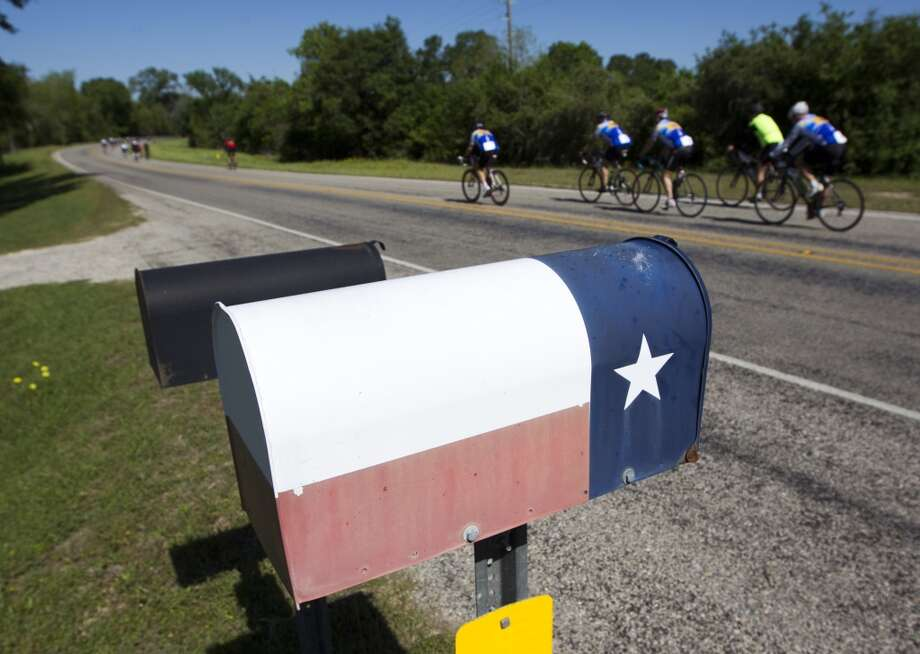 Cyclists pass a mailbox painted as a Texas Flag as they ride along FM 529 towards Bellville on route to Austin during the BP MS 150 on Saturday, April 20, 2013, in Houston.