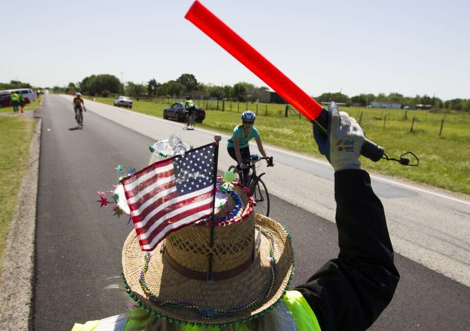 Barbara Burns directs cyclists to a break stop along FM 529 towards Bellville on route to Austin during the BP MS 150 on Saturday, April 20, 2013, in Houston.
