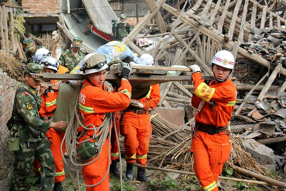Rescue workers carry an earthquake victim from his damaged home in Lushan county, China, where the powerful temblor killed scores, injured thousands and displaced tens of thousands. Photo: -, AFP/Getty Images