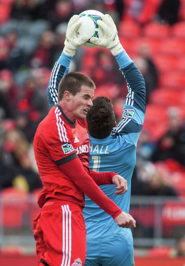 Houston Dynamo goal keeper Tally Hall snatches the ball in front of Toronto FC's Justin Braun during first half MLS action in Toronto, Saturday, April 20, 2013. (AP Photo/The Canadian Press, Jesse Johnston) Photo: Jesse Johnston, Associated Press / CP