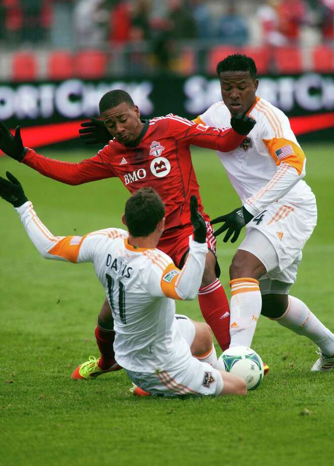 Toronto FC's Reggie Lambe is stripped of the ball by Houston Dynamo's Brad Davis, bottom, and Jermaine Taylor during first half MLS action in Toronto, Saturday, April 20, 2013. (AP Photo/The Canadian Press, Jesse Johnston) Photo: Jesse Johnston, Associated Press / CP