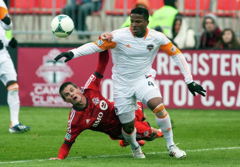 Toronto FC's Justin Braun grabs Houston Dynamo's Jermaine Taylor during first half MLS action in Toronto, Saturday, April 20, 2013. (AP Photo/The Canadian Press, Jesse Johnston) Photo: Jesse Johnston, Associated Press / CP