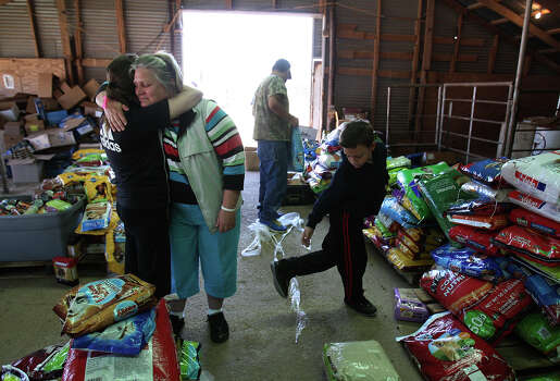 Jacki Arias (second from left) receives a hug from a neighbor, Mindy (no last name given) while picking up pet food to possibly feed their cat that remained in their home near the blast site. The Arias's home was less than a half-mile from the West Fertilizer Company explosion. Since Wednesday, the family has stayed with a relative and have been frustrated by the lack of clear information on when they could return to their home. Photo: Kin Man Hui, San Antonio Express-News / ©2013 San Antonio Express-News