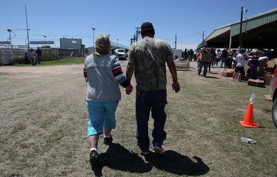 Pete (right) and Jacki Arias walk hand-in-hand with to the distribution center to pick up pet food to possibly feed their cat that remained in their home near the blast site. The Arias's home was less than a half-mile from the West Fertilizer Company explosion. Since Wednesday night, the family has stayed with a relative and have been frustrated by the lack of clear information on when they could return to their home. They were hoping to gain access to the home to at least drop off the food for their cat. Photo: Kin Man Hui, San Antonio Express-News / ©2013 San Antonio Express-News