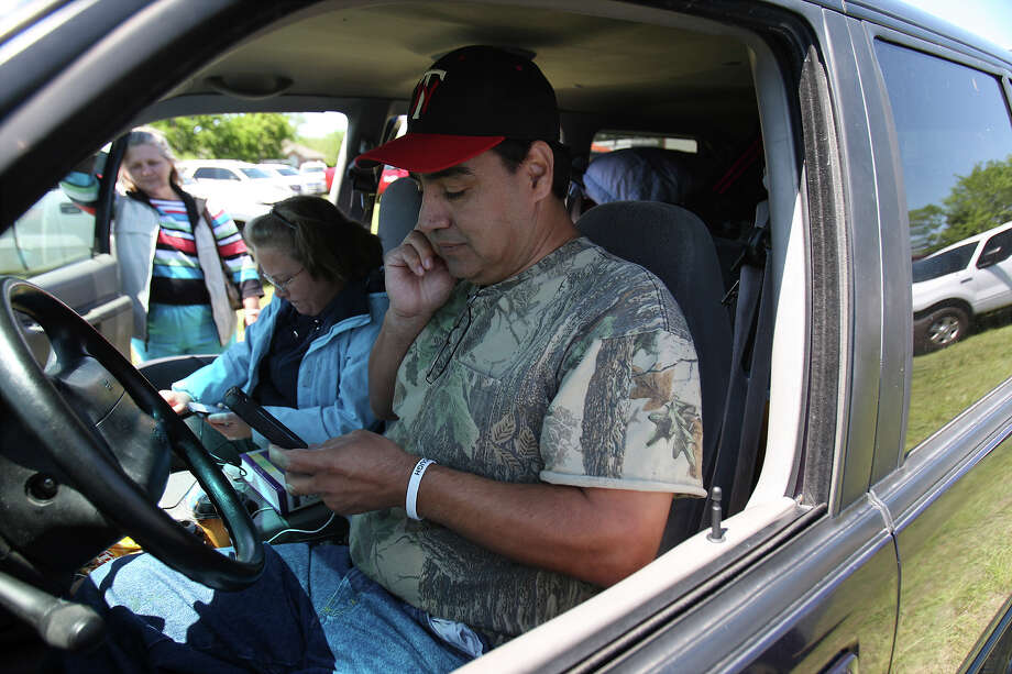 Pete Arias checks his phone for any updates about when he and his family could return to their home in West, Texas on Saturday, Apr. 20, 2013. The Arias's home was less than a half-mile from the West Fertilizer Company explosion. Since Wednesday night, the family has stayed with a relative and have been frustrated by the lack of clear information on when they could return to their home. Photo: Kin Man Hui, San Antonio Express-News / ©2013 San Antonio Express-News