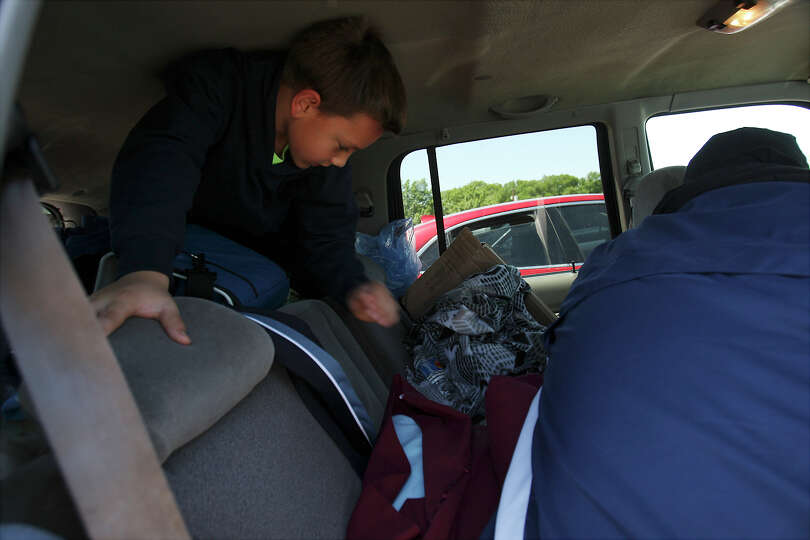 Eight-year-old Sam Arias crawls out of the back of the family vehicle while his father, Pete, gets h
