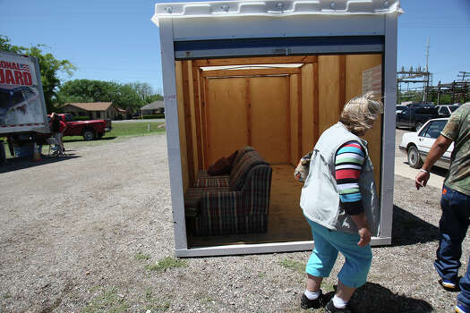 Jacki Arias walks past a storage trailer containing a sofa while visiting a community center to get pet food in West, Texas on Saturday, Apr. 20, 2013. The Arias's home was less than a half-mile from the West Fertilizer Company explosion. Since Wednesday night, the family has stayed with a relative and have been frustrated by the lack of clear information on when they could return to their home. Photo: Kin Man Hui, San Antonio Express-News / ©2013 San Antonio Express-News