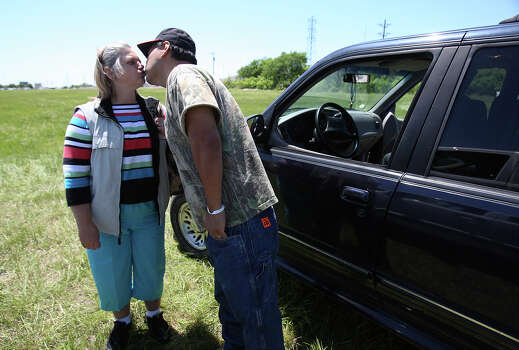 Pete Arias gives his wife, Jacki, a kiss during a pause in going from place to place in West, Texas to find information about when they could return to their home in West, Texas on Saturday, Apr. 20, 2013. The Arias's home was less than a half-mile from the West Fertilizer Company explosion. Since Wednesday, the family has stayed with a relative and have been frustrated by the lack of clear information on when they could return to their home. Photo: Kin Man Hui, San Antonio Express-News / ©2013 San Antonio Express-News