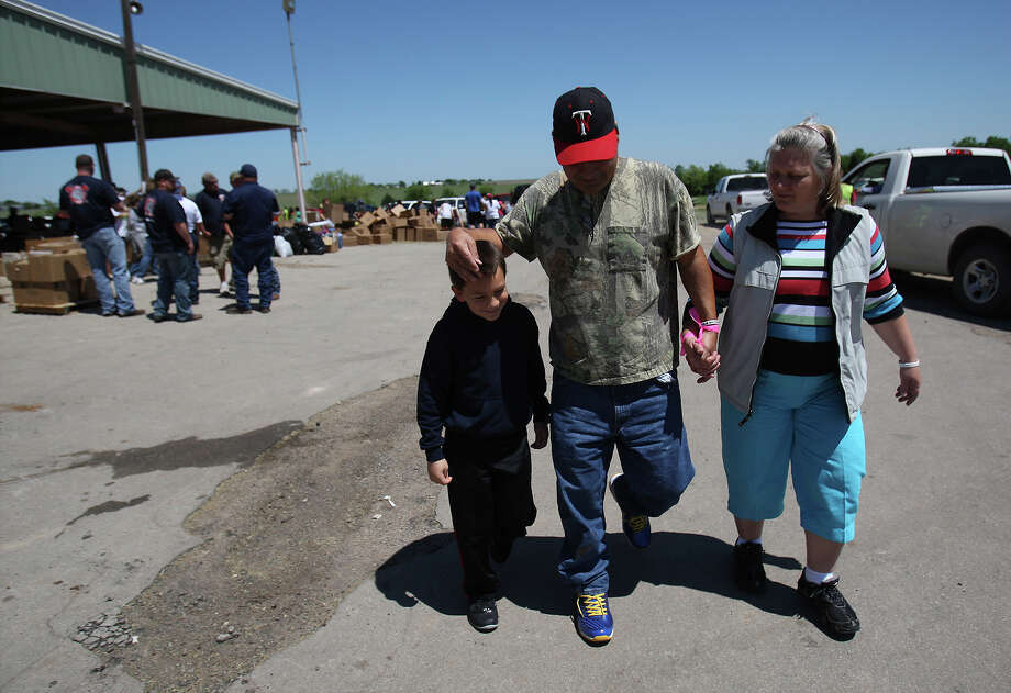 Pete and Jacki Arias along with their eight-year-old son, Sam, walk past the distribution center to pick up pet food to possibly feed their cat that remained in their home near the blast site. The Arias's home was less than a half-mile from the West Fertilizer Company explosion. Since Wednesday, the family has stayed with a relative and have been frustrated by the lack of clear information on when they could return to their home. They were hoping to gain access to the home to at least drop off the food for their cat. Photo: Kin Man Hui, San Antonio Express-News / ©2013 San Antonio Express-News