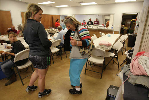 Jacki Arias shows off her make-shift outfit to fellow resident Rachel Hoffman at a community center in West, Texas on Saturday, Apr. 20, 2013. Hoffman had helped Arias the day before in getting the clothes after she and her family evacuated from their home near the West Fertilizer Company explosion. Since Wednesday, the family has stayed with a relative and have been frustrated by the lack of clear information on when they could return to their home. Photo: Kin Man Hui, San Antonio Express-News / ©2013 San Antonio Express-News