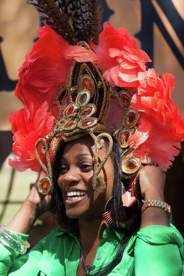Contrice Kendall tries on a Brazilian headdress during the 43rd annual Houston International Festival on Saturday, April 20, 2013, in Houston.  The highlight of the festival this year was the culture of South America with a focus on the art, music and cuisine of Brazil. Photo: J. Patric Schneider, For The Chronicle / © 2013 Houston Chronicle
