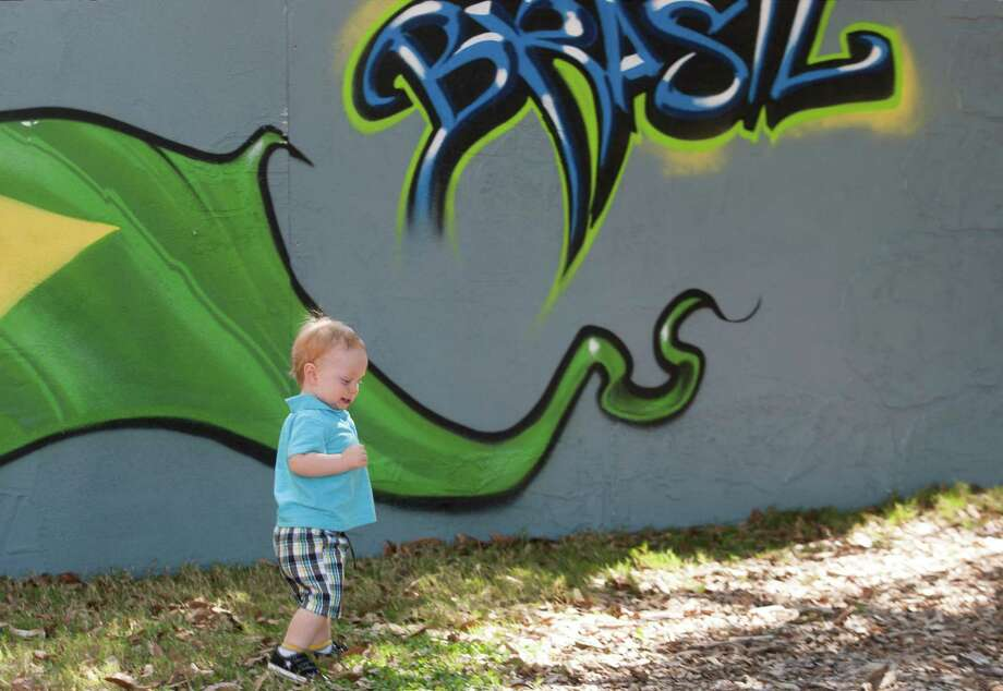 Thirteen-month-old Preston Doperalski walks by a wall painting during the 43rd annual Houston International Festival on Saturday, April 20, 2013, in Houston.  The highlight of the festival this year was the culture of South America with a focus on the art, music and cuisine of Brazil. Photo: J. Patric Schneider, For The Chronicle / © 2013 Houston Chronicle