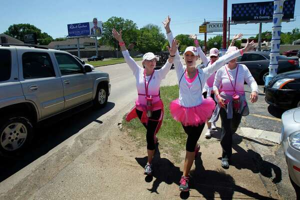 From left, Lisa Phillips, Sarah Judson, Wendy Wright, and Heidi Russell, react to honking vehicles as they walk along Richmond Avenue during the 6th Annual Avon Walk for Breast Cancer Houston Saturday, April 20, 2013, in Houston. The walk consisted of a total of 39 miles split into two days.