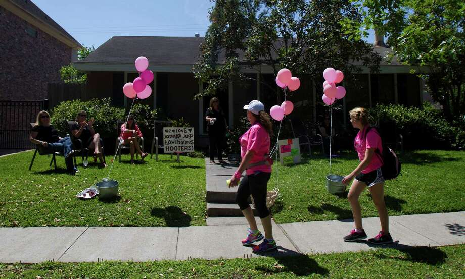 Kristal Caceres, left, and Jocelyn Westling, 15, right, walk in front of a supporters house on Auden Street during the 6th Annual Avon Walk for Breast Cancer Houston Saturday, April 20, 2013, in Houston. The walk consisted of a total of 39 miles split into two days. Photo: Cody Duty, Houston Chronicle / © 2013 Houston Chronicle
