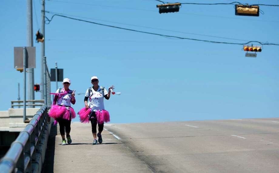 Lori mcConathy, left, and Deena Acord, right, make their way over the Edloe Street bridge during the 6th Annual Avon Walk for Breast Cancer Houston Saturday, April 20, 2013, in Houston. The walk consisted of a total of 39 miles split into two days. Photo: Cody Duty, Houston Chronicle / © 2013 Houston Chronicle
