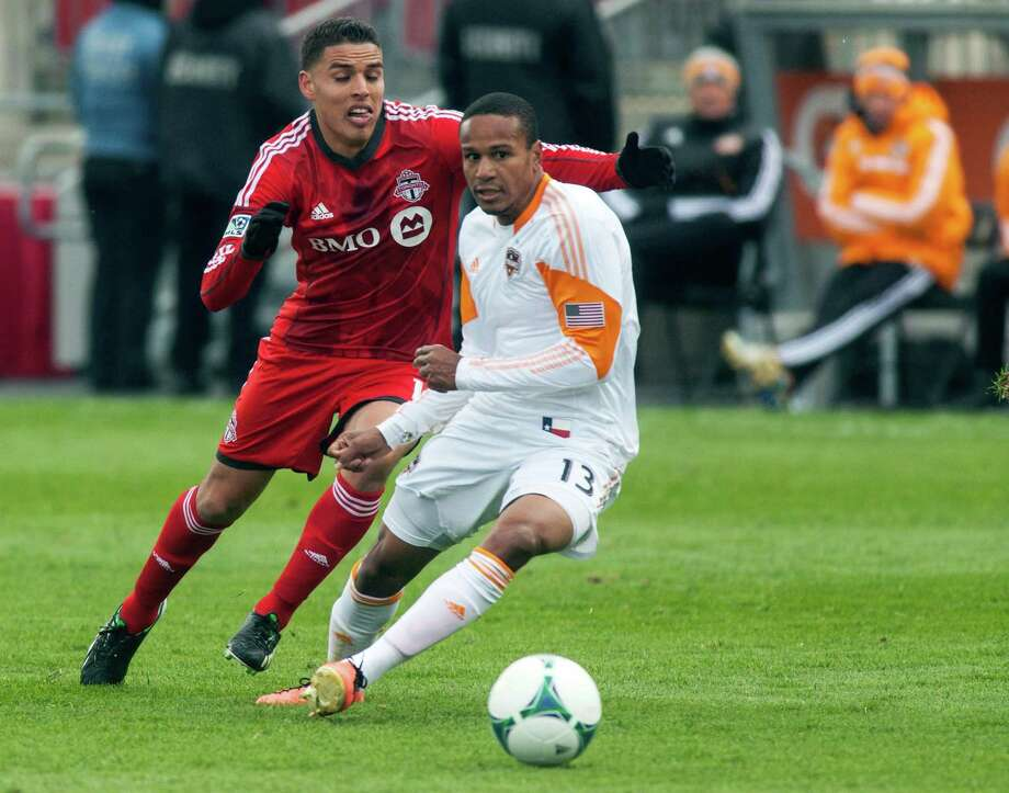 Toronto FC's Luis Silva, left, and Houston Dynamo's Ricardo Clark race for the ball during first half MLS action in Toronto, Saturday, April 20, 2013.(AP Photo/The Canadian Press, Jesse Johnston) Photo: Jesse Johnston, Associated Press / CP