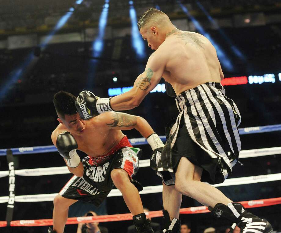 Omar Gonzales lands a blow to the head of Raul Martinez in a preliminary bout at the Alamodome on Saturday, April 20, 2013. Photo: Billy Calzada, Express-News / San Antonio Express-News