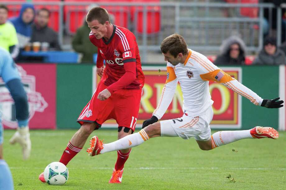 Toronto FC 's Justin Braun, left, puts in a cross past Houston Dynamo's Eric Brunner during second-half MLS soccer match action in Toronto, Saturday, April 20, 2013. (AP Photo/The Canadian Press, Chris Young) Photo: Chris Young, Associated Press / The Canadian Press