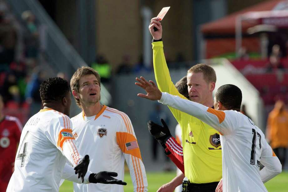 Referee Drew Fischer, second from right, shows a red card to Houston Dynamo's Jermaine Taylor, left, after a foul on Toronto FC 's Robert Earnshaw during second-half MLS soccer match action in Toronto, Saturday, April 20, 2013. (AP Photo/The Canadian Press, Chris Young) Photo: Chris Young, Associated Press / The Canadian Press