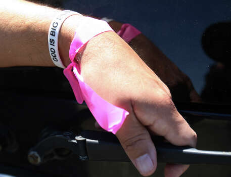 "Pete Arias is seen wearing a pink ribbon and a wrist band that states, ""God is big enough""  on Saturday, Apr. 20, 2013. The pink ribbon was put on at the distribution center in West, Texas to indicate an individual is picking up supplies. Arias's home was less than a half-mile from the West Fertilizer Company explosion. Since Wednesday night, he and his family have stayed with a relative and have been frustrated by the lack of clear information on when they could return to their home. Photo: Kin Man Hui, Express-News / ©2013 San Antonio Express-News"