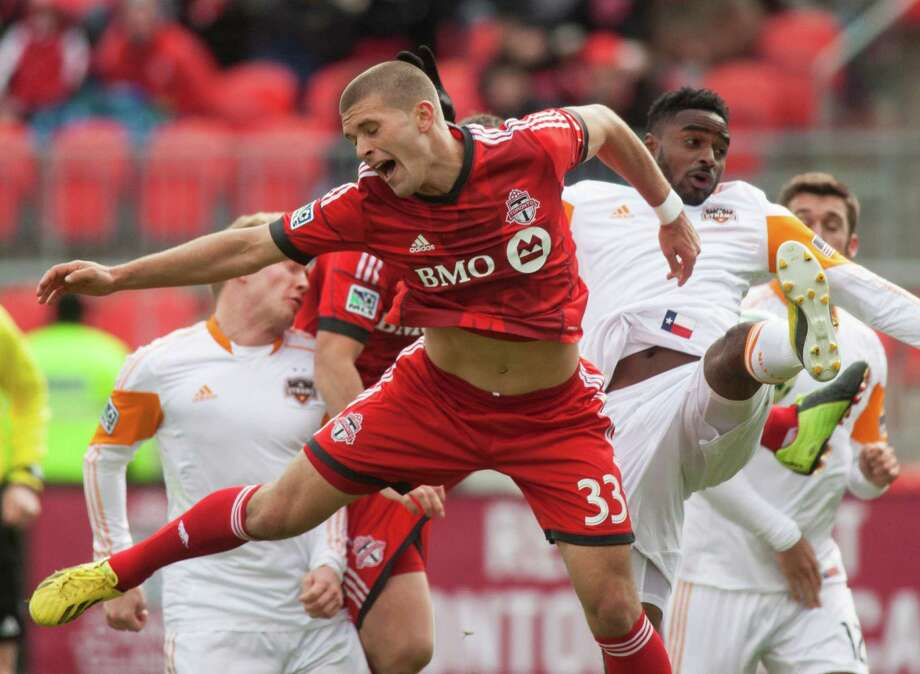 Toronto FC's Ryan Richter, front, and Houston Dynamo's Warren Creavalle react after colliding during the first half an MLS soccer game in Toronto, Saturday, April 20, 2013. The teams tied 1-1. (AP Photo/The Canadian Press, Jesse Johnston) Photo: Jesse Johnston, Associated Press / The Canadian Press
