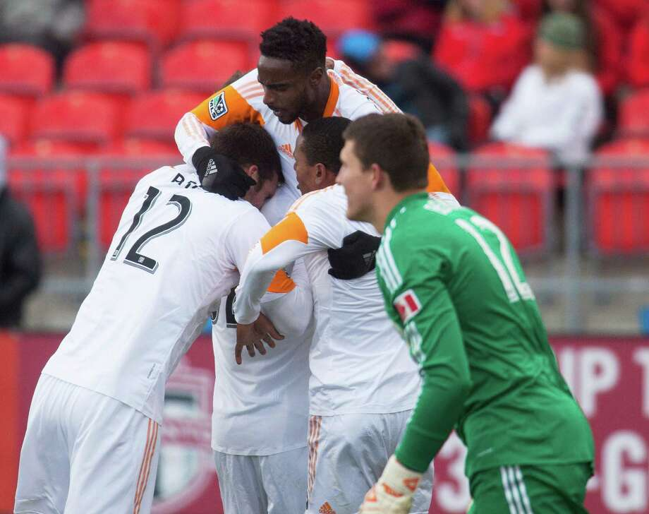 Toronto FC goalkeeper Joseph Bendik, right, stands nearby as Houston Dynamo's Warren Creavalle, top, is congratulated by teammates after scoring the game-tying goal in injury time during an MLS soccer game in Toronto, Saturday, April 20, 2013. The teams tied 1-1. (AP Photo/The Canadian Press, Jesse Johnston) Photo: Jesse Johnston, Associated Press / The Canadian Press