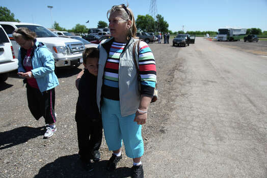 Jacki Arias (center) gets a hug from her eight-year-old son, Sam, as her daughter, Racheal (cq), walks past while visiting an community center in West, Texas on Saturday, Apr. 20, 2013. The Arias's home was less than a half-mile from the West Fertilizer Company explosion. Since Wednesday night, the family has stayed with a relative and have been frustrated by the lack of clear information on when they could return to their home. Photo: Kin Man Hui, Express-News / ©2013 San Antonio Express-News
