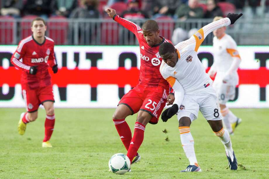 Toronto FC 's Jeremy Hall, front left, and Houston Dynamo's Kofi Sarkodie compete for the ball during the second half of an MLS soccer game in Toronto, Saturday, April 20, 2013. The teams tied 1-1. (AP Photo/The Canadian Press, Jesse Johnston) Photo: Chris Young, Associated Press / The Canadian Press
