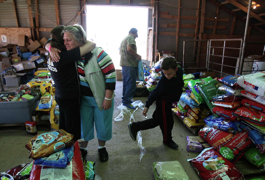 Jacki Arias (second from left) receives a hug from a neighbor, Mindy (no last name given) while picking up pet food to possibly feed their cat that remained in their home near the blast site. The Arias's home was less than a half-mile from the West Fertilizer Company explosion. Since Wednesday, the family has stayed with a relative and have been frustrated by the lack of clear information on when they could return to their home. Photo: Kin Man Hui, Express-News / ©2013 San Antonio Express-News