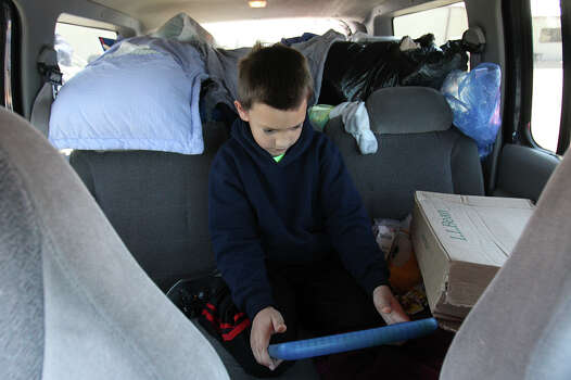 Eight-year-old Sam Arias sits alone in the back his parent's SUV that is filled with supplies in West, Texas on Saturday, Apr. 20, 2013. Sam's parents, Pete and Jacki Arias had been traveling to various community centers hoping to know when they could return to their home. The Arias's home was less than a half-mile from the West Fertilizer Company explosion. Since Wednesday night, the family has stayed with a relative and have been frustrated by the lack of clear information on when they could return to their home. Photo: Kin Man Hui, Express-News / ©2013 San Antonio Express-News