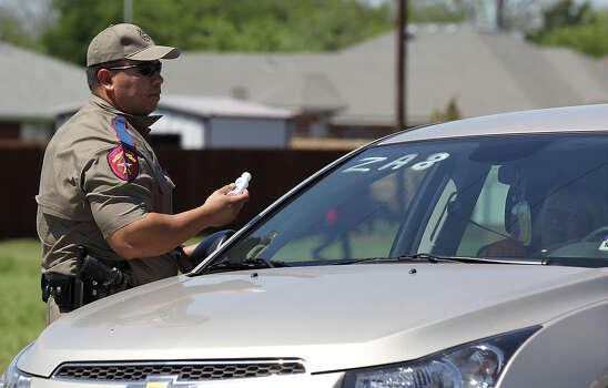 A law enforcement officer completes marking a vehicle for a resident who will be allowed to re-enter their home near the blast site in West, Texas on Saturday, Apr. 20, 2013. After several days of keeping the area clear for search and rescue and other safety concerns, officials were finally beginning the process of allowing families to return to their affected homes. Photo: Kin Man Hui, Express-News / ©2013 San Antonio Express-News