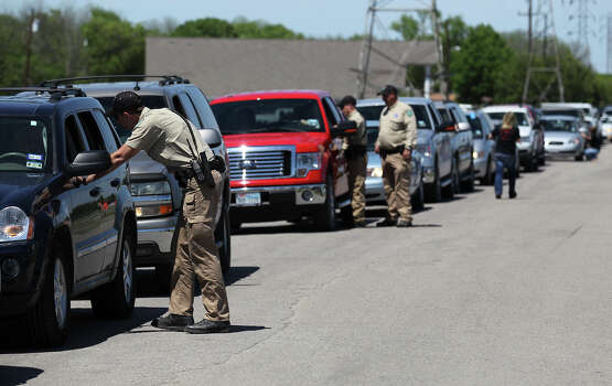 Law enforcement officials talk to residents in their vehicles about the procedure to re-enter their homes near the blast site in West, Texas on Saturday, Apr. 20, 2013. After several days of keeping the area clear for search and rescue and other safety concerns, officials were finally beginning the process of allowing families to return to their affected homes. Photo: Kin Man Hui, Express-News / ©2013 San Antonio Express-News