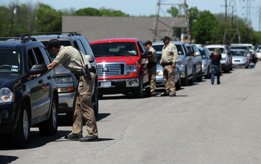Law enforcement officials talk to residents in their vehicles about the procedure to re-enter their