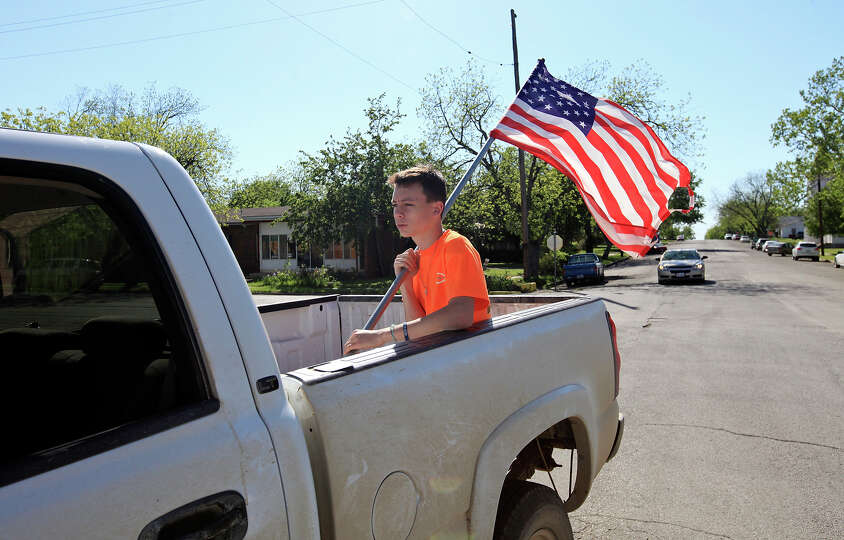 Kyle Sinkule, 16, holds an American flag while riding in the bed of a pickup, Saturday April 20, 201