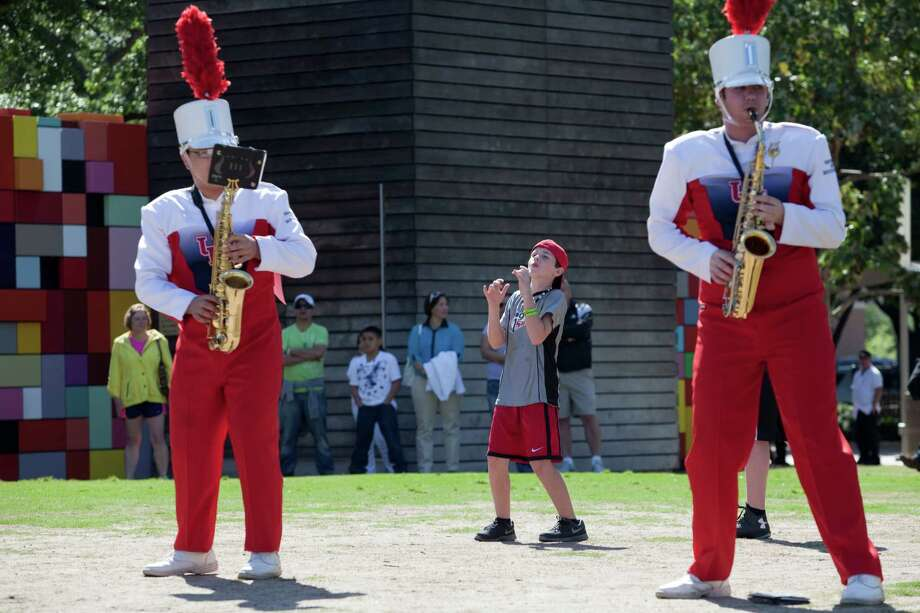 "Tyler Reed, 11, pantomimes playing saxophone along with the  University of Houston's Spirit of Houston Marching Band as they play April 20, 2013 in Houston at Discovery Green. The University of Houston's Spirit of Houston Marching Band played a four-hour performance. They performed a work titled ""En Masse"" by composer Daniel Bernard Roumain, who is doing a two-year residency at UH's Mitchell Center for the Arts. Saturday's concert featured about 150 members of the band as well as Roumain, who plays the violin. Photo: Eric Kayne, For The Chronicle / © 2013 Eric Kayne"