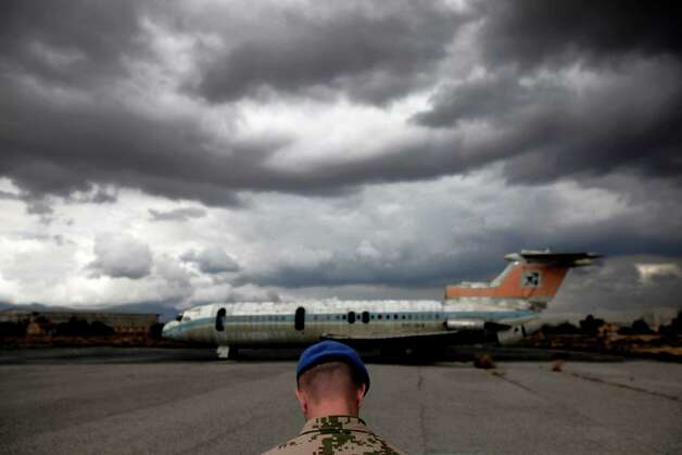 A UN soldier stands in front of a destroyed Cyprus airways plane at the war-torn UN buffer zone at the abandoned Nicosia airport in the divided capital, Friday, April 19, 2013. The abandoned airport whose grounds now serve as the headquarters for the United Nations peacekeeping force, is a stark reminder of the Cypru's decades-long ethnic division now overshadowed by the country's severe financial crisis. (AP Photo/Petros Karadjias) Photo: Petros Karadjias, Associated Press / AP