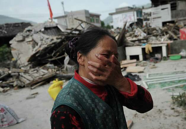A village woman reacts after her house was damaged by an earthquake in Lushan county, Ya'an, southwest China's Sichuan province on Saturday, April 20, 2013. The powerful earthquake struck the steep hills of China's southwestern Sichuan province Saturday, nearly five years after a devastating quake wreaked widespread damage across the region. (AP Photo) CHINA OUT Photo: Associated Press / COLOR CHINA PHOTO