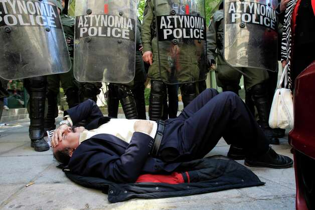 Manolis Lampsidis, ex-president of Thessalonikis' lawyers union, left, lies in front of riot police in Thessaloniki, Greece, on Saturday April 20, 2013, during a protest supporting two men arrested for allegedly taking part in an arson attack on a controversial gold mine operation in northern Greece. (AP Photo/Nikolas Giakoumidis) Photo: Nikolas Giakoumidis, Associated Press / AP