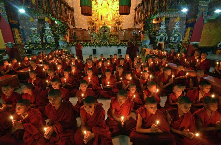 Young Buddhist monks pray for the speedy recovery of a 5-year-old girl who was raped and tortured in Delhi, in Bodhgaya, India, Saturday, April 20, 2013. Officials say the child is in serious condition after being raped and tortured by a man who held her in a locked room in India's capital for two days. Police say the girl went missing Monday and was found Wednesday by neighbors who heard her crying in a room in the same New Delhi building where she lives with her parents. (AP Photo/Manish Bhandari) Photo: Manish Bhandari, Associated Press / AP