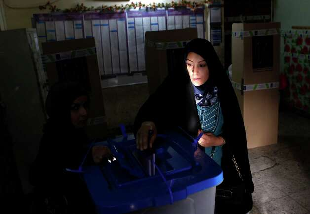 An Iraqi woman, the last voter in a polling center in the Karrada neighborhood, polling center casts her ballot just before polls closed in the country's provincial elections in Baghdad, Iraq, Saturday, April 20, 2013. Iraqis passed through security checkpoints and razor-wire cordons to vote in the country's first vote since the U.S. military withdrawal, marking an important test of the country's stability. (AP Photo/ Hadi Mizban) Photo: Hadi Mizban, Associated Press / AP