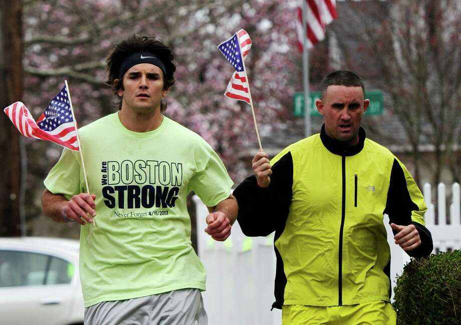 Mike Coppola and Eric Wayne run by Franklin Street with American flags and a 'Boston Strong' t-shirt on April 20, 2013 in Watertown, Massachusetts. Photo: Kevork Djansezian, Getty Images / 2013 Getty Images