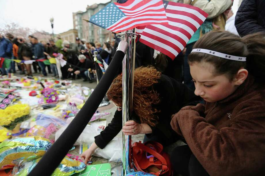 People gather at a makeshift memorial for victims near the site of the Boston Marathon bombings a day after the second suspect was captured on April 20, 2013 in Boston, United States.  A manhunt for Dzhokhar A. Tsarnaev, 19, a suspect in the Boston Marathon bombing ended after he was apprehended on a boat parked on a residential property in Watertown, Massachusetts. Photo: Mario Tama, Getty Images / 2013 Getty Images