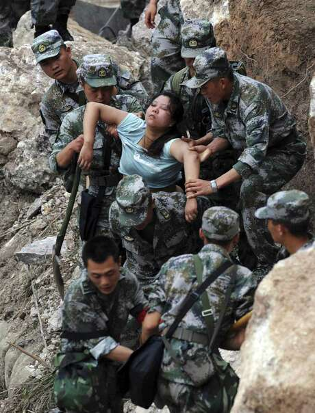 Rescuers pull an injured woman from debris in Baosheng Township, Lushan County, Sichuan province, China. Saturday's earthquake struck nearly five years after a devastating quake wreaked widespread damage across the region and the government was criticized for its response and rescue efforts. After Saturday's magnitude 7.0 quake, Prime Minister Li Keqiang flew to Lushan County and visited local hospitals. Photo: Jiang Hongjing / Associated Press