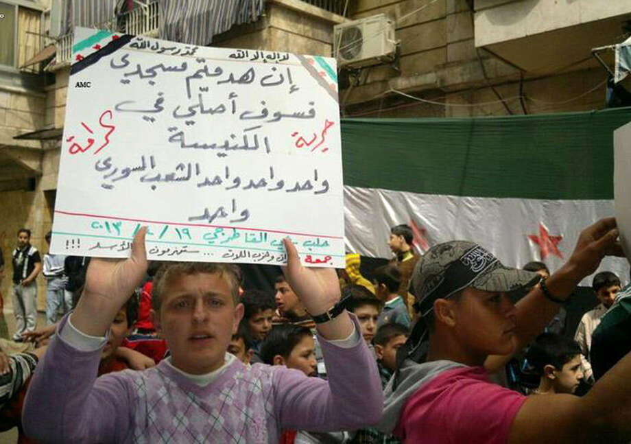"A man protesting Syrian President Bashar Assad's government holds a sign that says: ""If you destroy my mosque I'll pray at the church, one one one the Syrian people is one, freedom, dignity"" during a demonstration in Aleppo, Syria, on Friday. Photo: Anonymous / Associated Press"