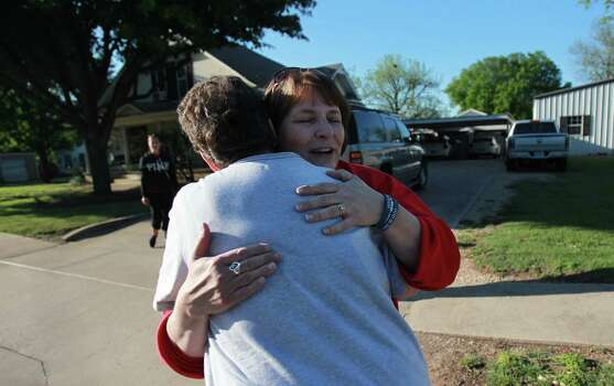 Debbie Pavlicek embraces a neighbor who stopped by and asked if they were ok during while re-entering the neighborhood on Saturday, April 20, 2013, in West. Authorities are starting the re-entry process in phases, and this afternoon Phase I began by allowing residents into parts of West less devastated. Photo: Mayra Beltran, Houston Chronicle / © 2013 Houston Chronicle