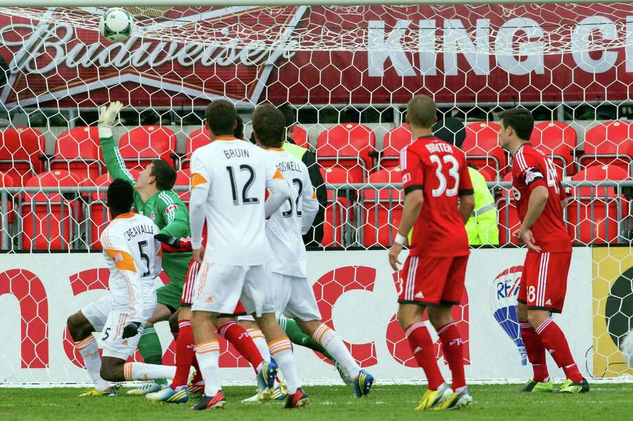 Dynamo defender Warren Creavalle (5) heads the ball over the outstretched arm of Toronto FC goalkeeper Joe Bendik to tie the game in stoppage time Saturday at BMO Field. Midfielder Ricardo Clark served up the assist on a corner kick. Photo: Chris Young, SUB / CP