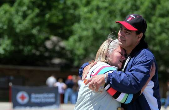 Jackie Arias, 49, is embraced by husband, Pete Arias, after visiting with friends at the Red Cross and try to decide where to live until residents are allowed back into the more devastated areas on Saturday, April 20, 2013, in West. Photo: Mayra Beltran, Houston Chronicle / © 2013 Houston Chronicle