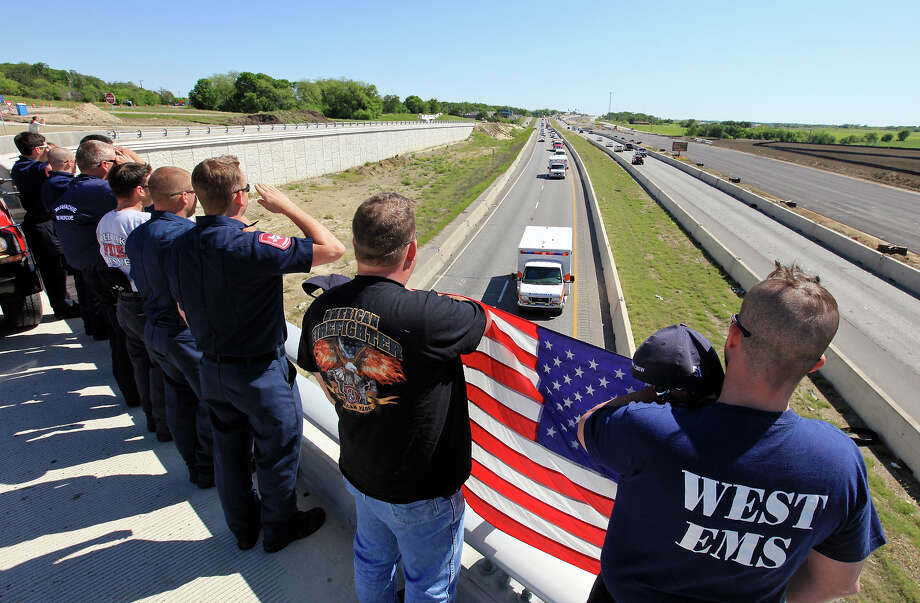 First responders line the rail of an overpass Saturday to pay tribute to fallen firefighters killed in Wednesday's fire and explosion at a fertilizer plant in West, as their remains are driven to Dallas for post-mortems. Photo: Edward A. Ornelas, Staff / © 2013 San Antonio Express-News