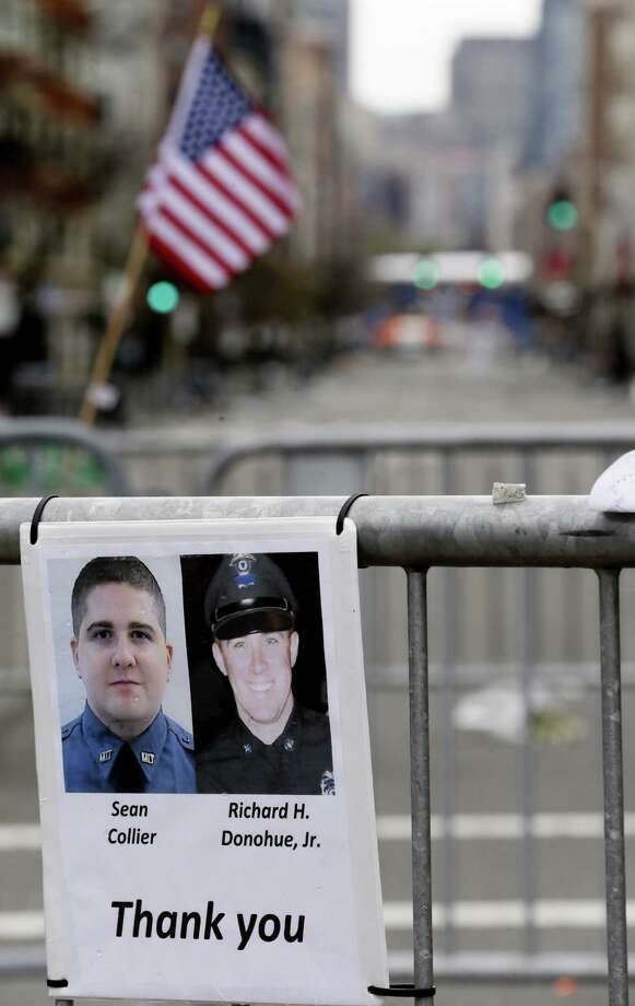 A sign with the photographs of Sean Collier, bottom left, a Massachusetts Institute of Technology officer killed, and Richard Donohue, a Boston Police officer who was shot and critically wounded, is seen at a makeshift memorial on Boylston Street, near the finish line of the Boston Marathon, Saturday, April 20, 2013, in Boston. Boston Marathon bombing suspect Dzhokhar Tsarnaev was captured late Friday evening in Watertown, Mass. (AP Photo/Julio Cortez) Photo: Julio Cortez